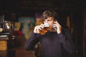Man talking on mobile phone while glass of beer