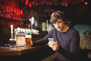 Man using mobile phone with beer glass in hand