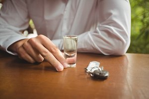 Man holding glass of tequila shot in bar counter