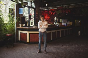 Man standing with arms crossed in bar