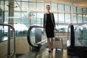 Businesswoman near escalator with luggage