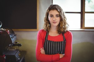 Confident waitress standing with arm crossed in café