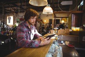 Man using digital tablet at counter