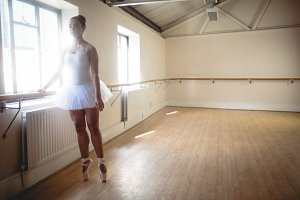 Ballerina practising ballet dance at barre