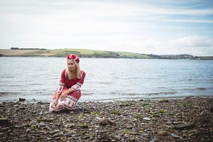 Blonde woman wearing a flower tiara sitting near a river