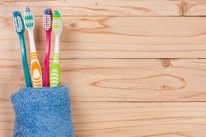 toothbrushes on the light wooden background with copy space for your text. Top view
