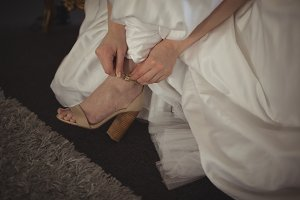 Close-up of bride wearing shoes