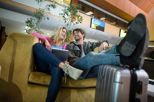 Smiling couple interacting with each other in waiting area