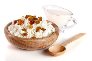 Cottage cheese with raisins and sour cream in a wooden bowl isolated on a white background