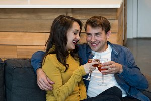 Couple drinking red wine while sitting on the sofa in living room