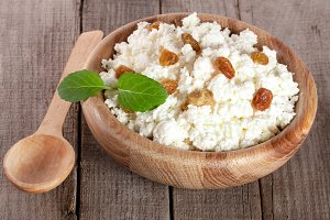 Cottage cheese with raisins in a wooden bowl on a wooden background