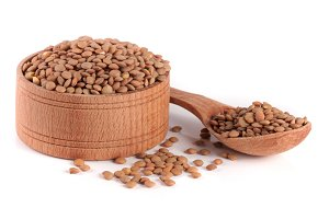 Lentils in a wooden bowl with a spoon isolated on a white background