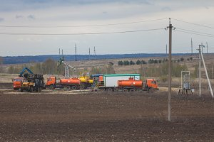 Oil pumpjack and fuel trucks among grassy field at sunny day