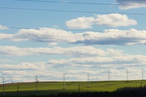 Summer lanscape with electricity pylons and lines at field, sunny day