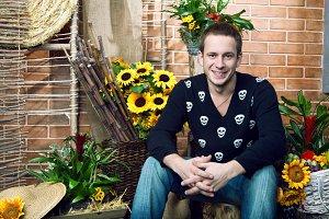 Handsome man sitting near flowerpots