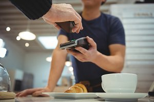 Customer making contactless payment in coffee shop