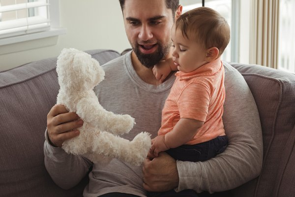 Father and baby playing with teddy…