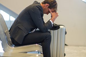 Tense businessman sitting in waiting area with luggage