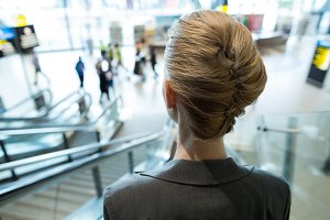 Rear view of businesswoman moving down on escalator