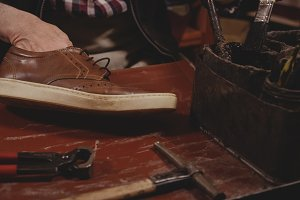 Shoemaker applying glue on shoe