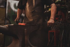 Blacksmith working on hot metal using hammer to shape