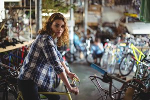 Portrait of beautiful mechanic trying bicycle