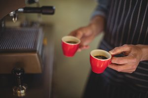 Mid section of waiter holding coffee cups at counter