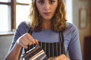 Portrait of beautiful waitress preparing coffee at counter