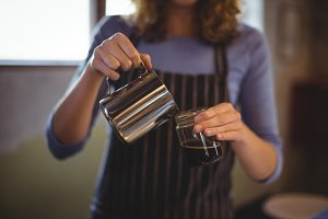 Mid section of waitress preparing coffee at counter