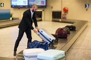 Businessman picking his luggage from baggage claim area