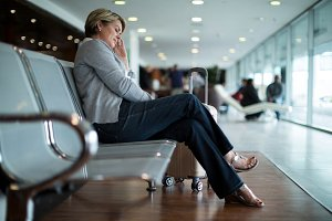Businesswoman sleeping on chair in waiting area
