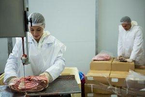 Female butcher cutting meat with meat cutting machine