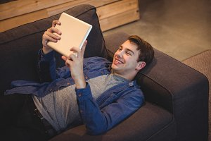 Smiling man lying on sofa using digital tablet in living room