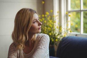 Beautiful woman looking through window in living room