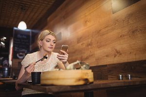 Woman using mobile phone while eating sushi