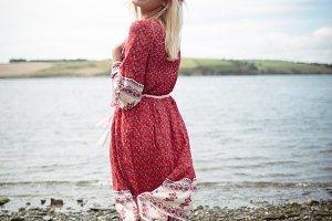 Blonde woman wearing a flower tiara standing near a river