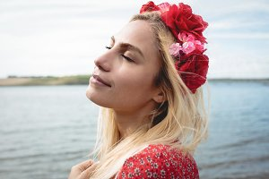 Blonde woman wearing a flower tiara standing near a river