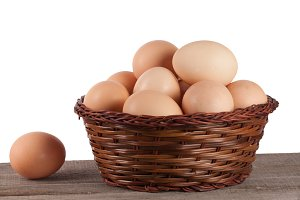 eggs in a wicker basket on a wooden board on a white background