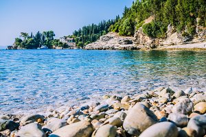 Pebble beach near Kalami with pine and cypress trees and an yacht at anchor in a bay on background. Corfu Island, Greece