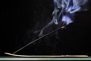 Incense stick smolders and emits intensive smoke