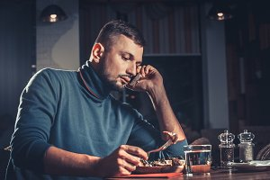 Man eating and speaking on mobile phone