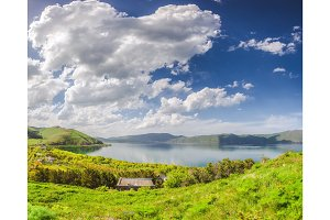 Meadow, lake and blue sky