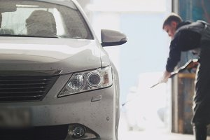 Worker washes the car in workshop - manual labour