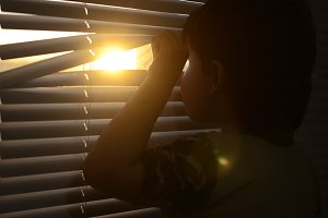 boy opens the shutters and looks at the sun