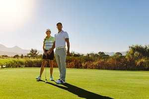Male and female golfers at field