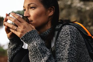 Young female hiker drinking coffee