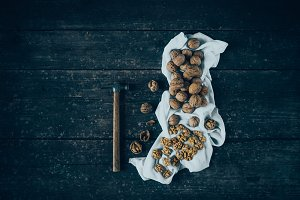 Walnuts with hammer on rustic table