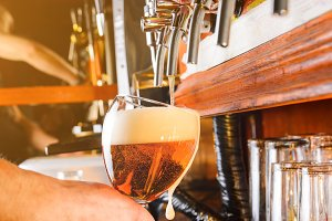 Barman is serving beer from faucet