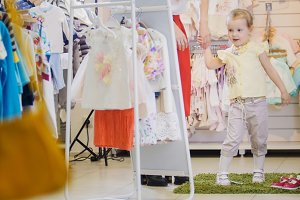 Little girl holding mother's hand and looks in the mirror in store