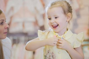 Happy little girl tries on summer shirt in store